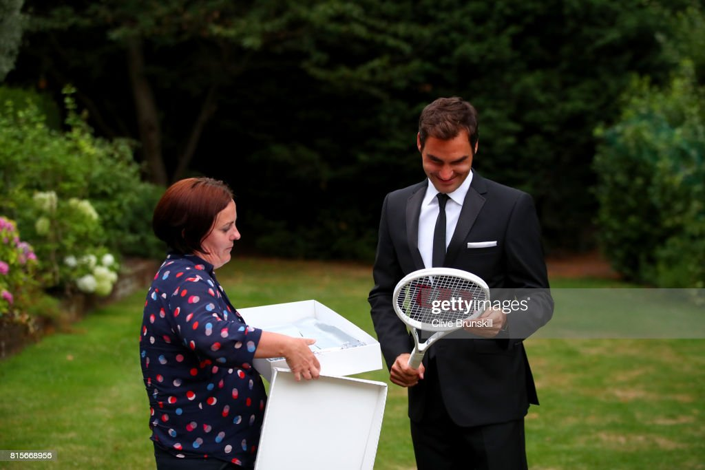 Roger Federer of Switzerland celebrates his Wimbledon record with an exclusive commemorative '8' Wilson tennis racket next to Joanne Thomas Kemp after his victory against Marin Cilic of Croatia on day thirteen of the Wimbledon Lawn Tennis Championships at the All England Lawn Tennis and Croquet Club on July 16, 2017 in London, England.