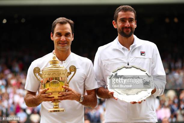 Roger Federer of Switzerland celebrates victory with the trophy alongside runnerup Marin Cilic of Croatia after the Gentlemen's Singles final on day...