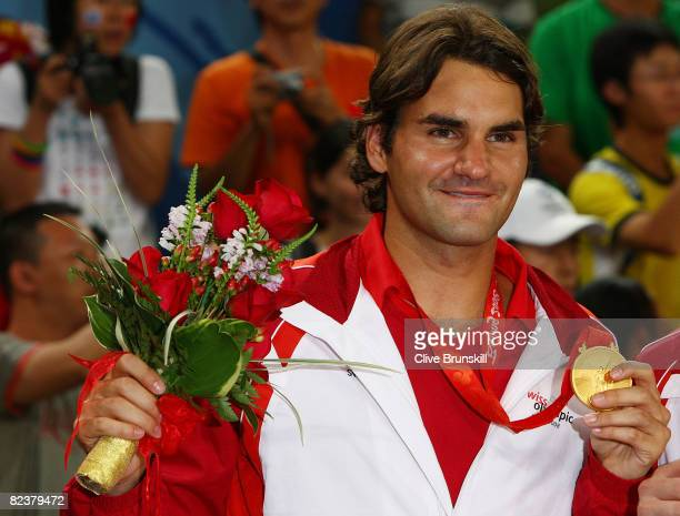 Roger Federer of Switzerland celebrates with his gold medal won with partner Stanislas Wawrinka after defeating Thomas Johansson and Simon Aspelin of...