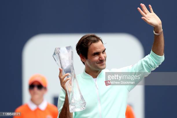 Roger Federer of Switzerland celebrates with the Butch Buchholz Trophy after defeating John Isner during the men's final of the Miami Open Presented...