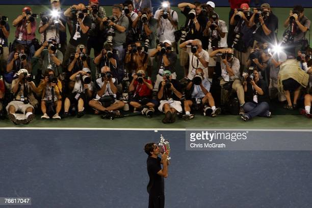 Roger Federer of Switzerland celebrates with the trophy after defeating Novak Djokovic of Serbia by a score of 76 76 64 to win the Men's Singles...