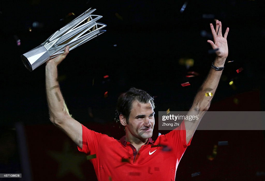 Roger Federer of Switzerland celebrates with the trophy after winning the final against Gilles Simon of France during the day 8 of the Shanghai Rolex Masters at the Qi Zhong Tennis Center on October 12, 2014 in Shanghai, China.