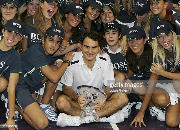 Roger Federer of Switzerland celebrates with the trophy as he is surrounded by ball kids and model ball girls after defeating Fernando Gonzalez of...