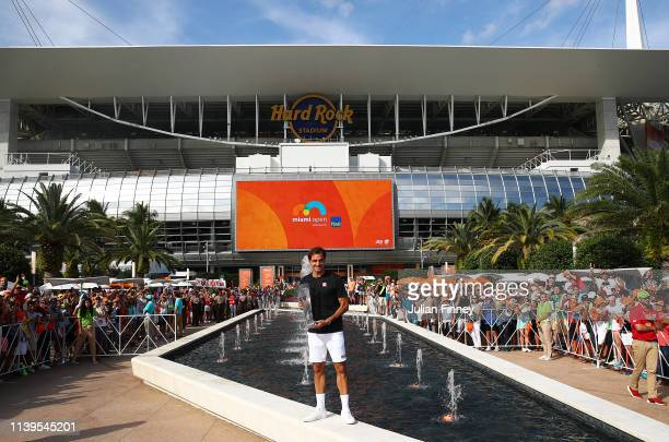 Roger Federer of Switzerland celebrates with the winners trophy after his final win against John Isner of USA during day fourteen of the Miami Open...