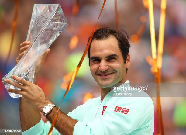Roger Federer of Switzerland celebrates with the winners trophy against John Isner of USA in the final during day fourteen of the Miami Open tennis...