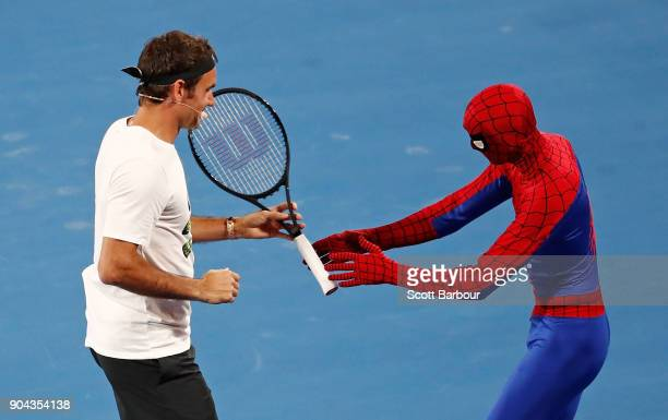 Roger Federer of Switzerland gives his tennis racquet to SpiderMan at the annual Kids Tennis Day ahead of the 2018 Australian Open at Melbourne Park...