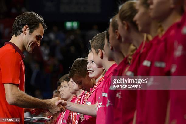 Roger Federer of Switzerland greets ball girls and ball boys after he won his final against David Goffin of Belgium at the Swiss Indoors ATP tennis...
