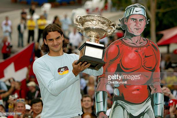 Roger Federer of Switzerland greets fans and holds up the trophy after winning the Australian Open Grand Slam against Marat Safin of Russia during...