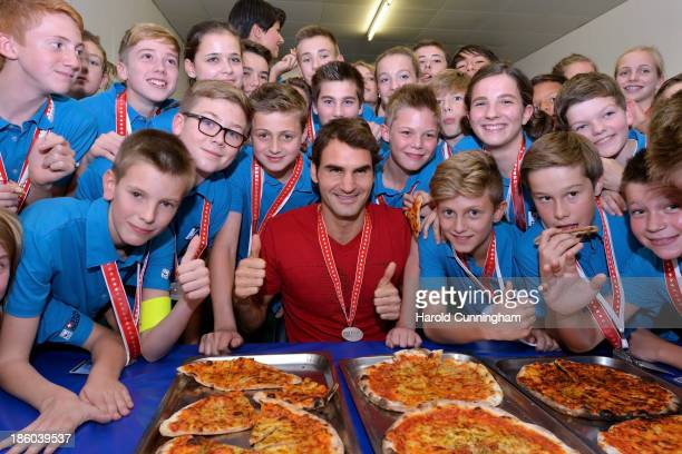 Roger Federer of Switzerland hands out pizza as he celebrates with the ball boys the end of the Swiss Indoors ATP Tennis at St Jakobshalle on October...