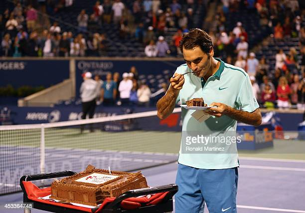 Roger Federer of Switzerland has a piece of his birthday cake after a quarterfinals win against David Ferrer of Spain during Rogers Cup at Rexall...