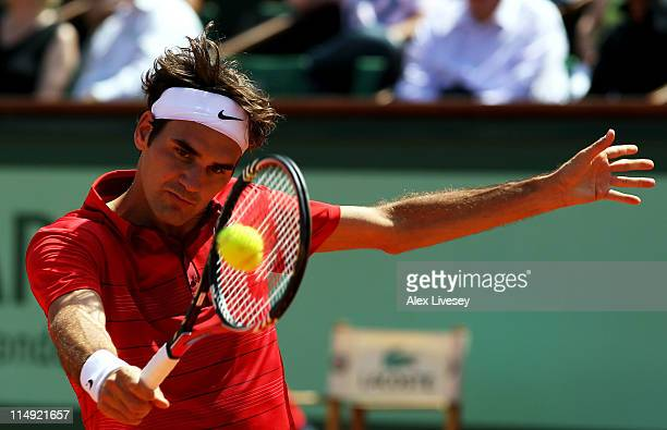 Roger Federer of Switzerland hits a backhand during the men's singles round four match between Stanislas Wawrinka of Switzerland and Roger Federer of...