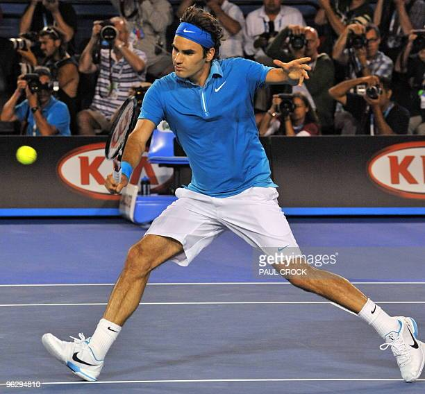 Roger Federer of Switzerland hits a volley return against Andy Murray of Britain in their men's singles final on day 14 of the Australian Open tennis...