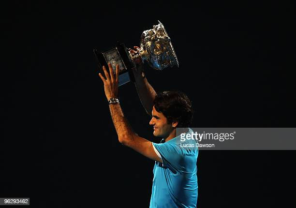 Roger Federer of Switzerland holds aloft the Norman Brookes Challenge Cup after his men's final match against Andy Murray of Great Britain during day...