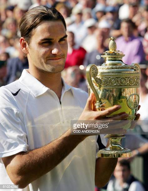 Roger Federer of Switzerland holds his trophy after defeating Andy Roddick of the US in their mens' singles match at the 118th Wimbledon Tennis...