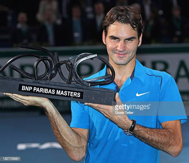 Roger Federer of Switzerland holds the championship trophy after defeating JoWilfried Tsonga of France in the finals of the BNP Paribas Masters at...