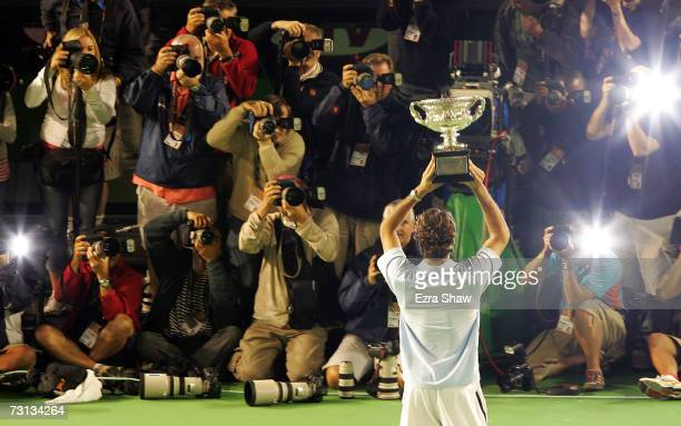 Roger Federer of Switzerland holds the trophy after winning his men's final match against Fernando Gonzalez of Chile on day fourteen of the...