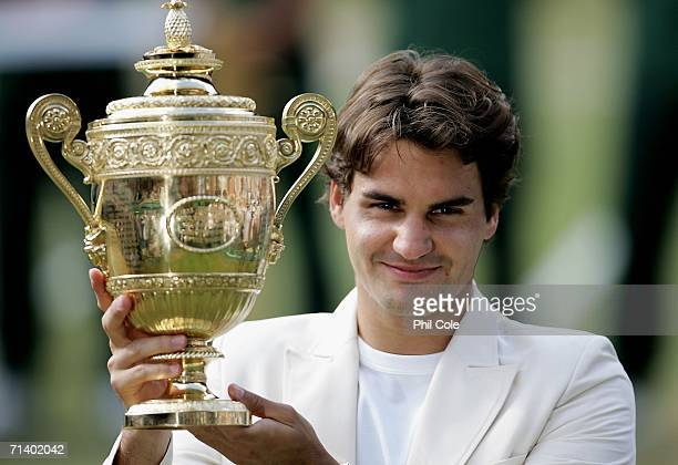 Roger Federer of Switzerland holds the trophy after winning the Men's final against Rafael Nadal of Spain on day thirteen of the Wimbledon Lawn...