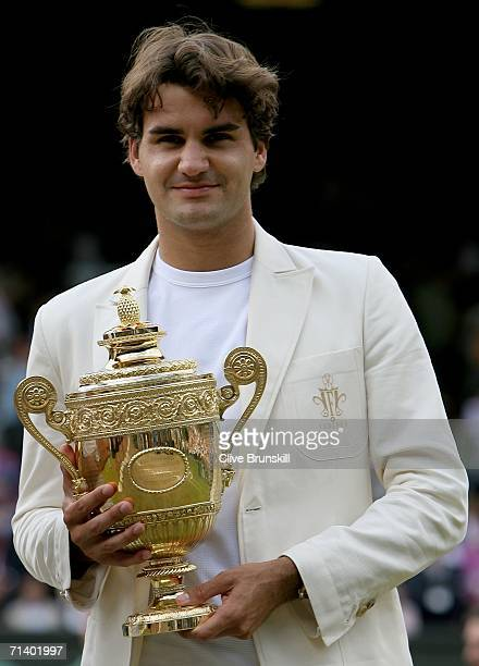 Roger Federer of Switzerland holds the trophy after winning then Men's final against Rafael Nadal of Spain on day thirteen of the Wimbledon Lawn...