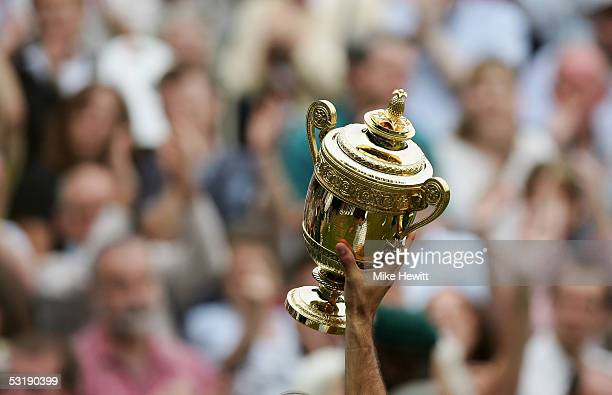 Roger Federer of Switzerland holds the trophy high after winning in straight sets against Andy Roddick of the USA in the Mens Singles final during...