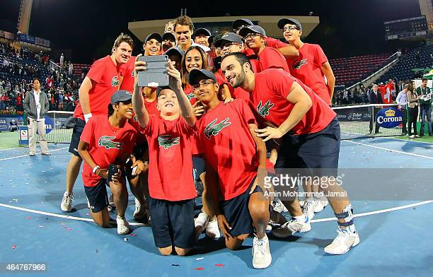 Roger Federer of Switzerland holds the trophy with the ball boy after winning the final match against Novak Djokovic of Serbia during men's singles...