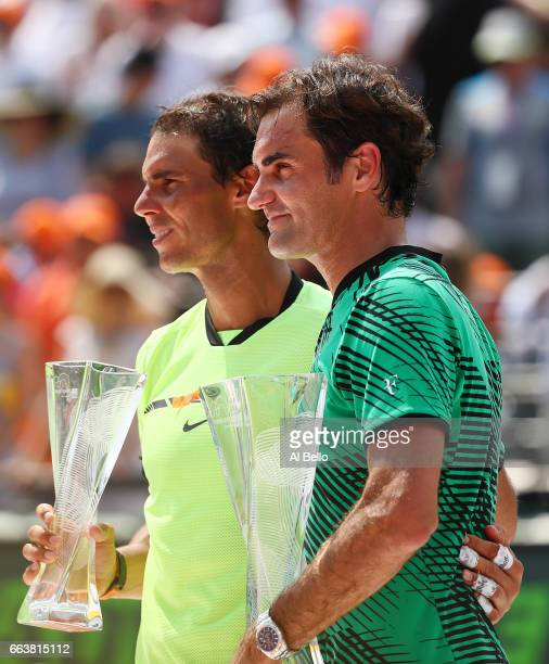 Roger Federer of Switzerland holds the winner's trophy after defeating Rafael Nadal of Spain with the runners up trophy after the Men's Final and day...