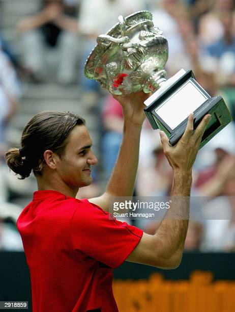 Roger Federer of Switzerland holds up the Australian Open Trophy after his victory against Marat Safin of Russia during the Mens Singles Final during...