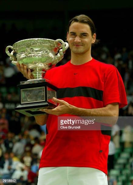 Roger Federer of Switzerland holds up the Australian Open Trophy after victory against Marat Safin of Russia during the Mens Singles Final during day...