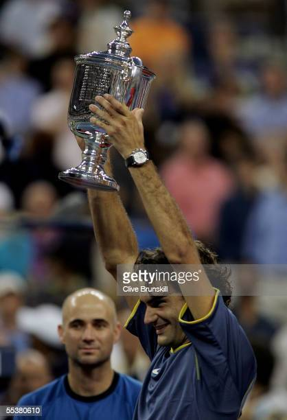 Roger Federer of Switzerland holds up the championship trophy as runner up looks on after Federer defeated Agassi in the men's final of the US Open...