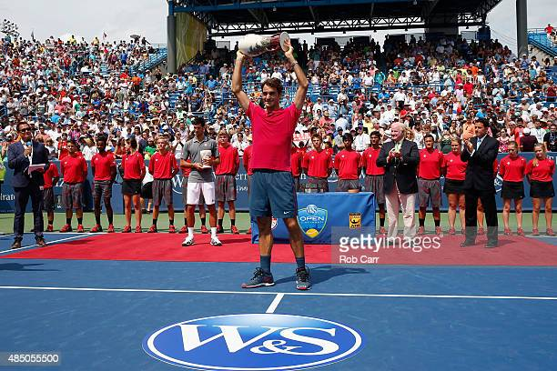 Roger Federer of Switzerland holds up the trophy after defeating Novak Djokovic of Serbia to win the mens singles final at the Western & Southern...