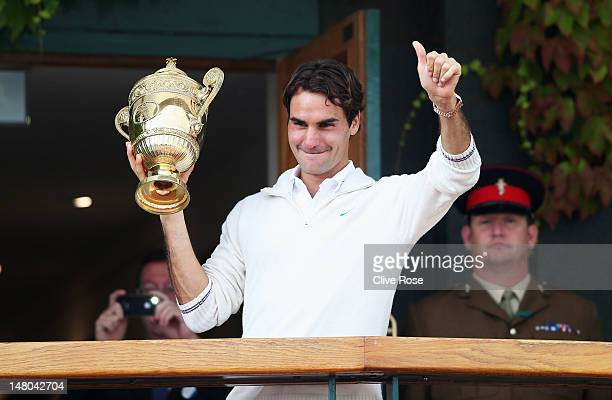 Roger Federer of Switzerland holds up the winner's trophy and gives a thumbs up to the crowd after winning his Gentlemen's Singles final match...