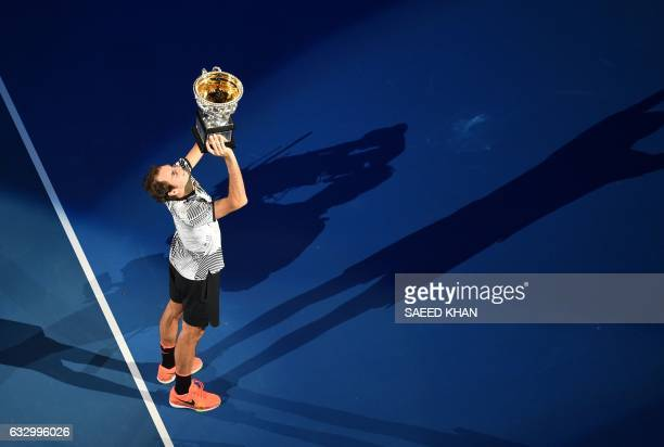 Roger Federer of Switzerland holds up the winner's trophy during a victory lap following his win over Rafael Nadal of Spain in the men's singles...