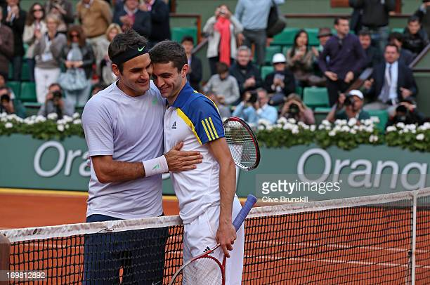 Roger Federer of Switzerland hugs Gilles Simon of France after their Men's Singles match during day eight of the French Open at Roland Garros on June...