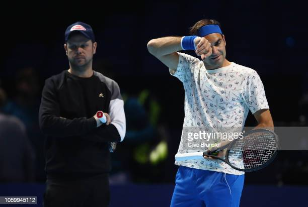 Roger Federer of Switzerland in action watched by Severin Luthi during a training session prior to the Nitto ATP World Tour Finals at O2 Arena on on...