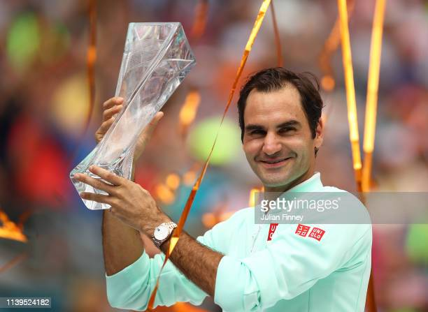 Roger Federer of Switzerland in celebrates with the winners trophy against John Isner of USA in the final during day fourteen of the Miami Open...