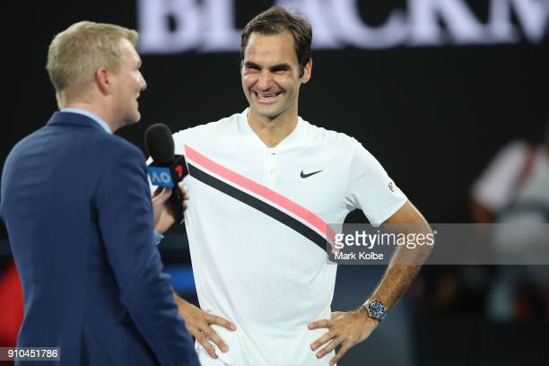Roger Federer of Switzerland is interviewed by commentator Jim Courier after winning his semifinal match against Hyeon Chung of South Korea on day 12...