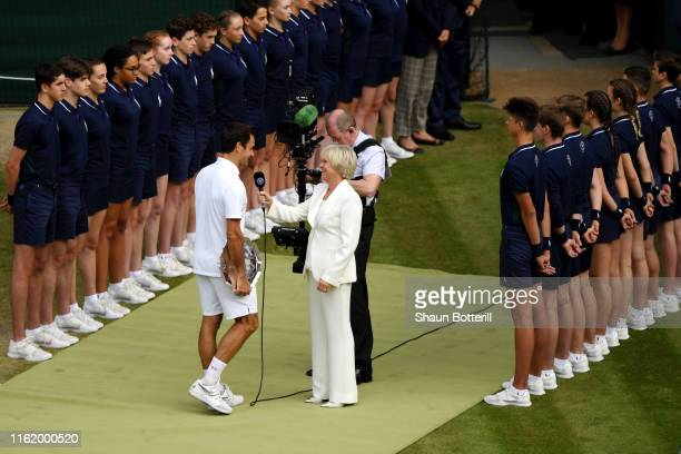 Roger Federer of Switzerland is interviewed by Sue Barker on court after his Men's Singles final against Novak Djokovic of Serbia during Day thirteen...