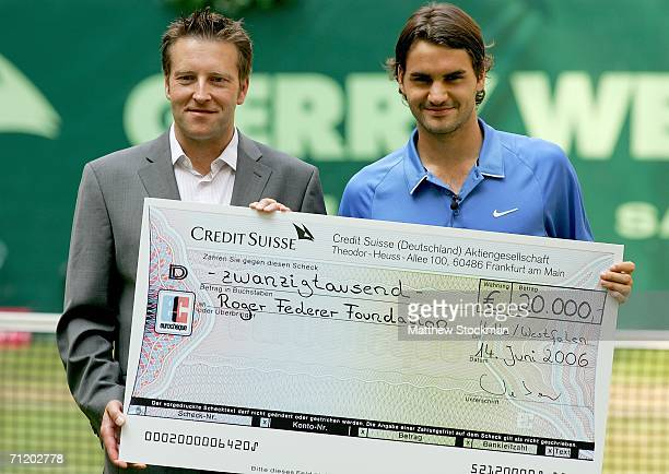 Roger Federer of Switzerland is presented a check by Ralf Weber for his foundation after his match against Rohan Bopanna of India June 14 2006 during...