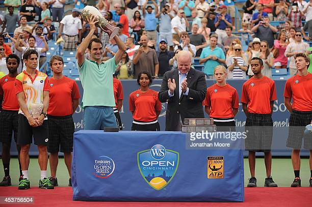 Roger Federer of Switzerland is presented the winner's trophy by John F Barrett Chairman President and Chief Executive Officer of Western Southern...