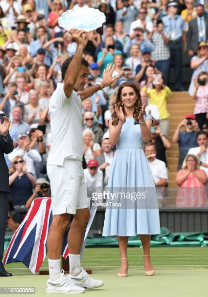 Roger Federer of Switzerland is presented with the runnersup trophy by Catherine Duchess of Cambridge after his Men's Singles final against Novak...