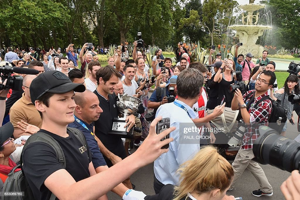 Roger Federer of Switzerland (C) is surrounded by fans during a photo opportunity with the championship trophy the day after winning the Australian Open men's singles tennis final for this 18th career Grand Slam in Melbourne on January 30, 2017. / AFP / PAUL