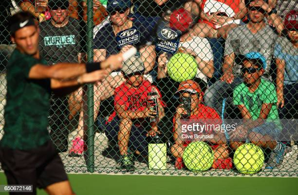 Roger Federer of Switzerland is watched by a wall of fans as he hits during a practice session on day four of the BNP Paribas Open at Indian Wells...