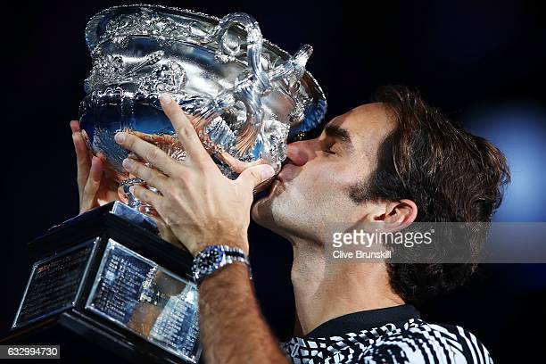 Roger Federer of Switzerland kisses the Norman Brookes Challenge Cup after winning the Men's Final match against Rafael Nadal of Spain on day 14 of...