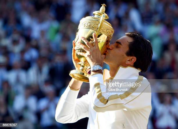 Roger Federer of Switzerland kisses the trophy after victory during the men's singles final match against Andy Roddick of USA on Day Thirteen of the...