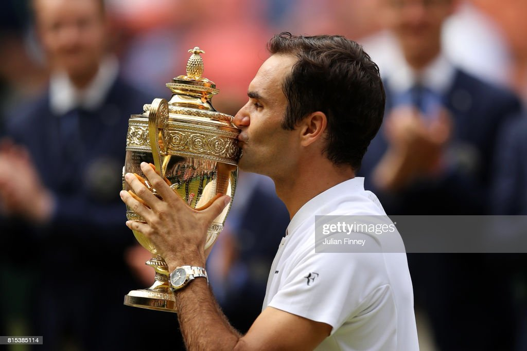 Roger Federer of Switzerland kisses the trophy as he celebrates victory after the Gentlemen's Singles final against Marin Cilic of Croatia on day thirteen of the Wimbledon Lawn Tennis Championships at the All England Lawn Tennis and Croquet Club at Wimbledon on July 16, 2017 in London, England.