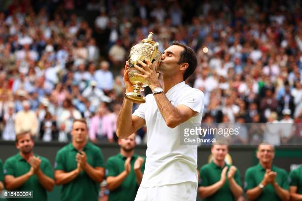 Roger Federer of Switzerland kisses the trophy as he celebrates victory after the Gentlemen's Singles final against Marin Cilic of Croatia on day...