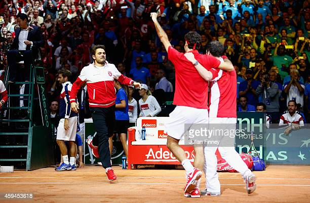 Roger Federer of Switzerland leads the celebrations after defeating Richard Gasquet of France as Stanislas Wawrinka of Switzerland and Captain...