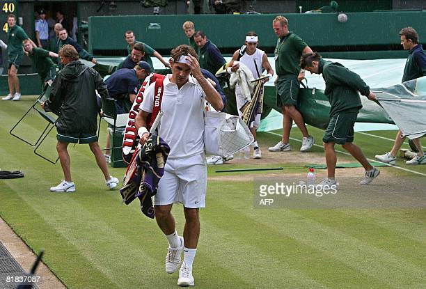 Roger Federer of Switzerland leaves Centre Court for a second rainbreak as he plays against Rafael Nadal of Spain in the Men's Singles Final during...