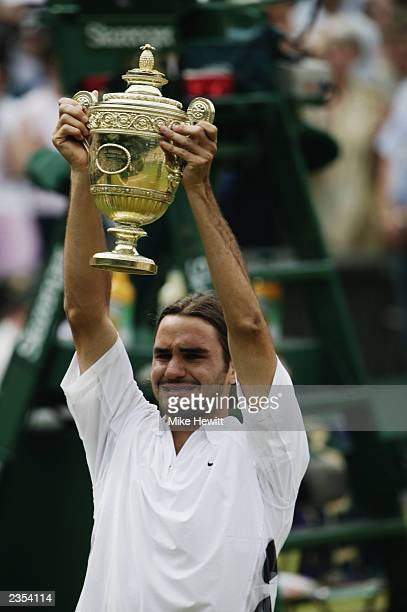 Roger Federer of Switzerland lifts the trophy after his victory over Mark Philippoussis of Australia in the Men's Singles Final during the final day...