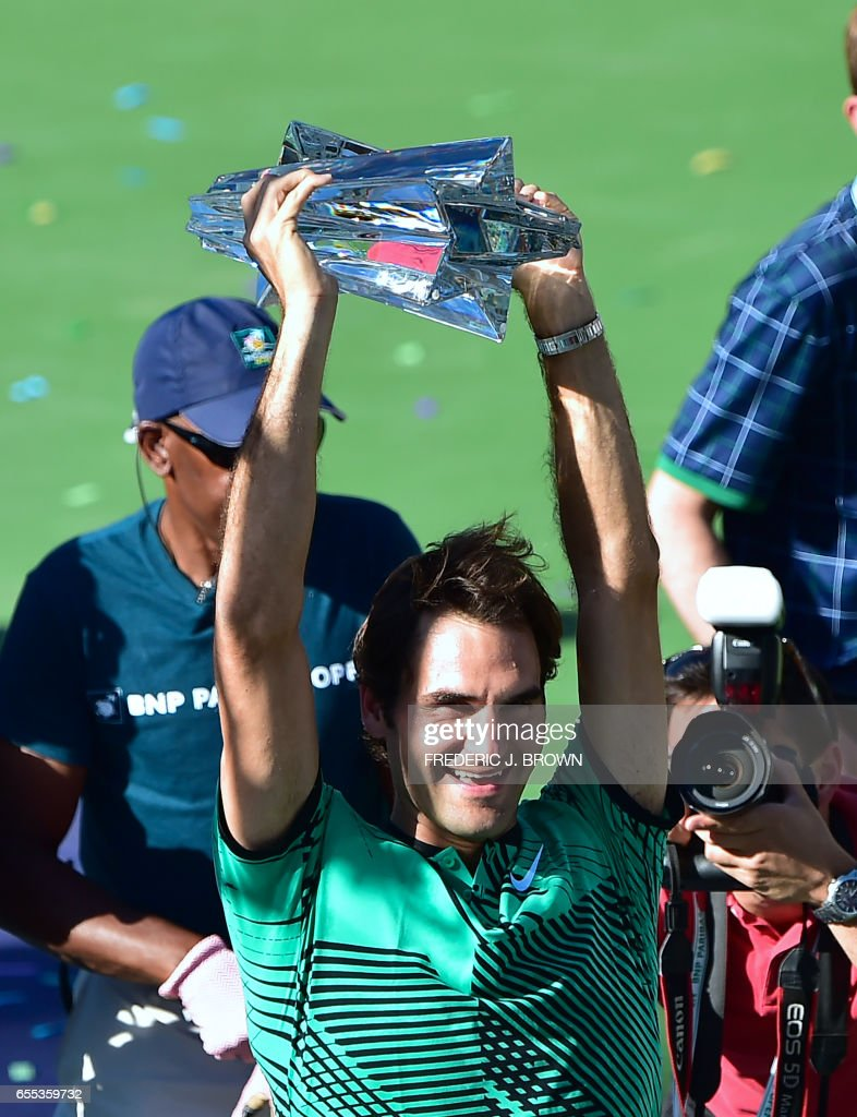 TOPSHOT - Roger Federer of Switzerland lifts the trophy following victory over compatriot Stan Wawrinka in the men's singles final at the ATP Indian Wells Masters in Indian Wells, California on March 19, 2017. Federer defeated Wawrinka 6-4, 7-5. /