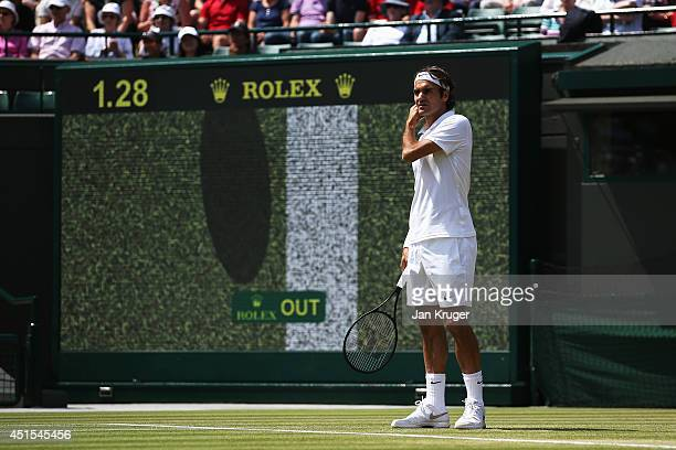 Roger Federer of Switzerland looks on as a hawk eye review is displayed on screen behind him during his Gentlemen's Singles fourth round match...